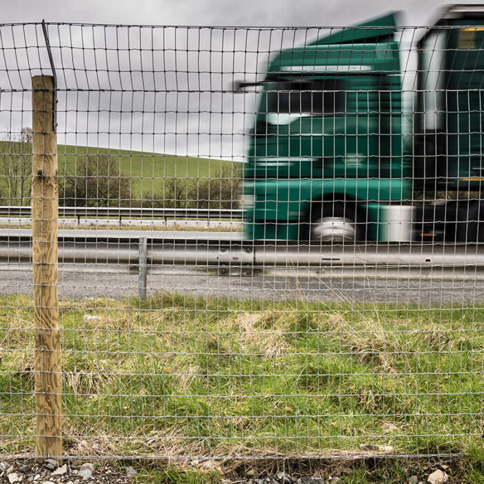 green lorry passing badger fencing